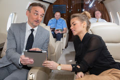 Business team traveling in corporate jet and discussing a presen Stock Image