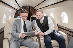 Business team traveling in corporate jet and discussing a presen Stock Photo