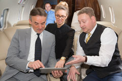 Business team traveling in corporate jet Stock Photo