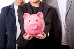 Business team-two men and woman holding piggybank Stock Photography