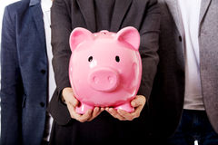 Business team-two men and woman holding piggybank Royalty Free Stock Photo