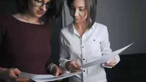 Business team of two women working with documents, discussing financial results and analyzing statistics stock video footage