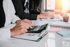 Business team using calculator and laptop computer to work with financial data stock photo