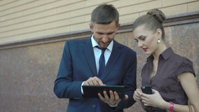 Business team using electronic tablet outside offices building. 4K stock footage