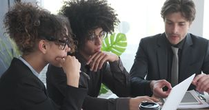 Business team using laptop at office meeting. Young business team using laptop while discussing at office conference stock footage