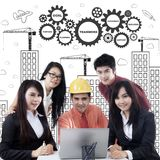 Business team with laptop and scribbles Stock Image
