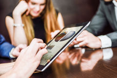 Business team using tablet computer to work with financial data. Close-up of a modern business team using tablet computer to work with financial data Royalty Free Stock Photos