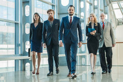 Business team walking in glass building. Business team walking in modern glass office building Stock Photo