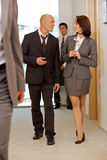Business team walking thru corridor and talking Stock Photos