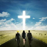 Business team walking toward a cross. Back view of three businesspeople walking on the road toward a cross Royalty Free Stock Photo