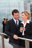 Business team watching mobile phone outdoor Stock Photos