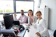 Business team waving hands at office. Corporate, technology and people concept - business team with tablet pc and computers waving hands at office royalty free stock images