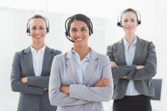 Business team wearing headsets and standing arms crossed Royalty Free Stock Images