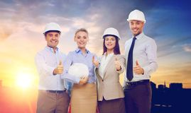 Business team in white hard hats showing thumbs up. Business, architecture and building concept - happy team of architects in white hard hats showing thumbs up Royalty Free Stock Image
