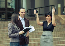 Business team winning outdoors at meeting. Business people at meeting outdoors talking with a happy client with hands up in sign of victory Stock Photos