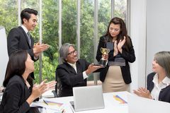 Business team winning trophy in the office . Businessman with te. Amwork in award and successful showing trophy and rewarded for in the office. asian people royalty free stock photography