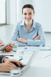 Business team at work and female executive smiling Royalty Free Stock Photos