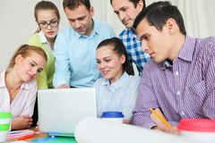 Business team work together. Looking at one laptop at workplace Royalty Free Stock Images