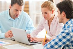 Business team work together. Looking at one laptop at workplace Stock Photo