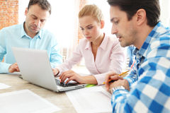 Business team work together. Looking at one laptop at workplace Stock Image