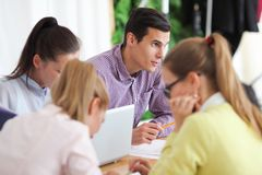 Business team work together. At workplace, focus on young man Stock Photography