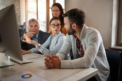 Business team workers in discussion at computer Royalty Free Stock Photography