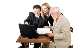 A business team working (4). A business team looking at a laptop Royalty Free Stock Photos