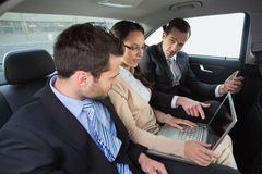 Business team working in the back seat. In the car Stock Photos