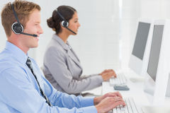 Business team working on computers and wearing headsets Royalty Free Stock Images