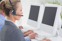 Business team working on computers and wearing headsets Stock Images