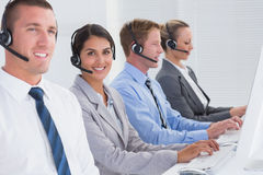 Business team working on computers and wearing headsets Royalty Free Stock Photos