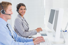 Business team working on computers and wearing headsets Stock Photos
