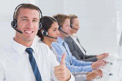 Business team working on computers and wearing headsets Royalty Free Stock Photography