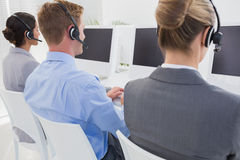Business team working on computers and wearing headsets Stock Photo