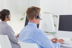 Business team working on computers and wearing headsets Stock Photography
