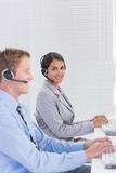 Business team working on computers and wearing headsets Stock Image
