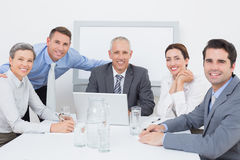 Business team working happily together on laptop Royalty Free Stock Image