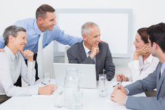 Business team working happily together on laptop Stock Image