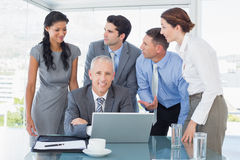 Business team working happily together on laptop Royalty Free Stock Photography