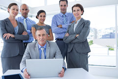 Business team working happily together on laptop Stock Photo