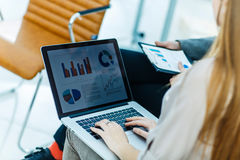 Business team working on laptop with financial schedules in the workplace. Closeup of business team working on laptop with financial schedules in the workplace Royalty Free Stock Image