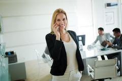Portrait of businesswoman making call while business people working at background royalty free stock images