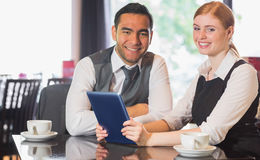 Business team working on tablet pc together in a cafe royalty free stock image