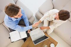 Business team working together on the couch shaking hands Stock Photos