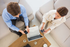 Business team working together on the couch using their smartphones Stock Photo