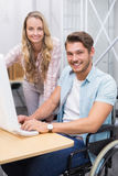 Business team working together at desk smiling at camera Stock Image