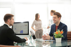 Business team working together to achieve better results. Business partners discussing in meeting hall with their collegues on the background Royalty Free Stock Photos