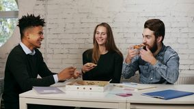 Business team of young people enjoying pizza together in the office, millennials group talking having fun sharing lunch stock video footage