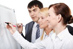 Business teamwork. Three businesspeople drawing something on a whiteboard Royalty Free Stock Photos