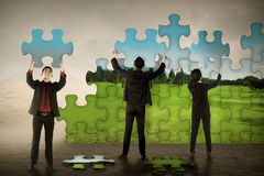 Business teamwork assembling puzzle pieces create green environt Royalty Free Stock Images